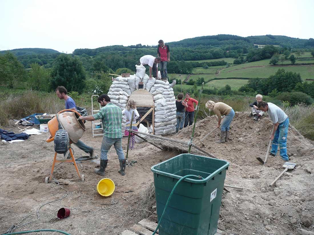 Een groep mensen bouwt met zandzakken een earth dome op Lotussy