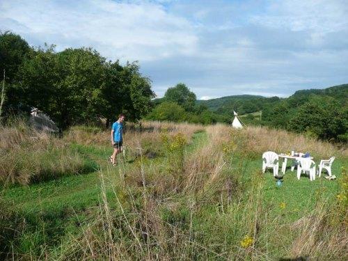 Blik over natuurcamping Lotussy. In de verte loopt iemand over het terrein.